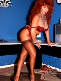 Busty radhead secretary in stockings posing on office table