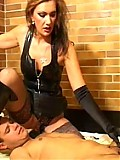 Serious leather mistress punishes male slave's cock and balls