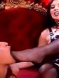 Mistress in black stockings makes a cute slave open her mouth and suck her captor's toes