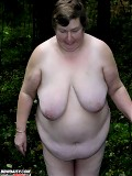 Very fat old grandmother gets naked in the forest