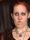 Redheaded gothic girl posing in a photostudio