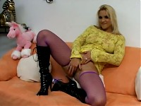 Hot blonde bimbo plays on couch