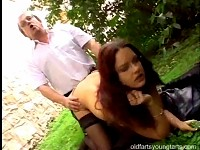 Brunette girl tasting old man his cumload in a public park